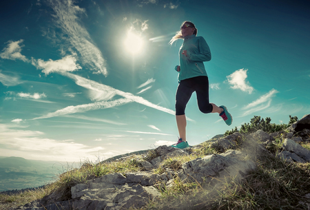 Foto de Female running in mountains under sunlight. - Imagen libre de derechos
