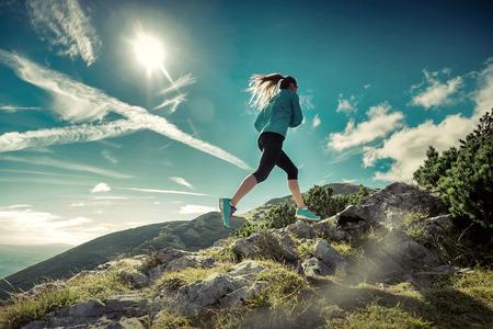 Photo pour Female running in mountains under sunlight. - image libre de droit