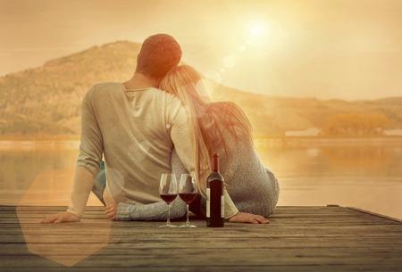 Foto de Romantic Couple sitting on the pier with red wine. - Imagen libre de derechos