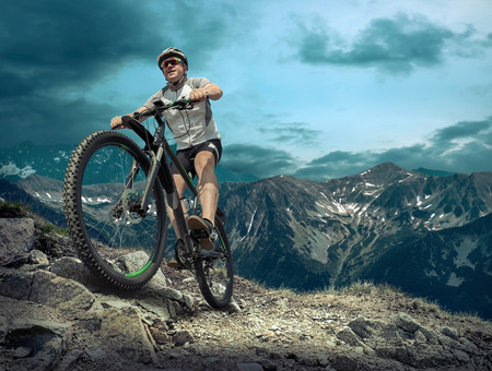Photo pour Man in helmet and glasses stay on the bicycle under sky with clouds. - image libre de droit