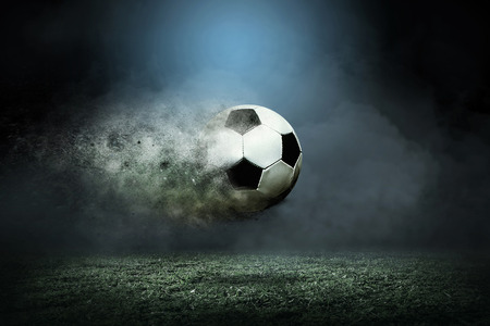 Foto de Moving soccer ball around splash drops on the stadium field. - Imagen libre de derechos