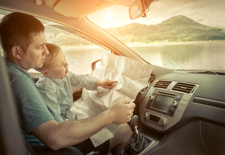 Photo pour Father and son looking on map in car - image libre de droit