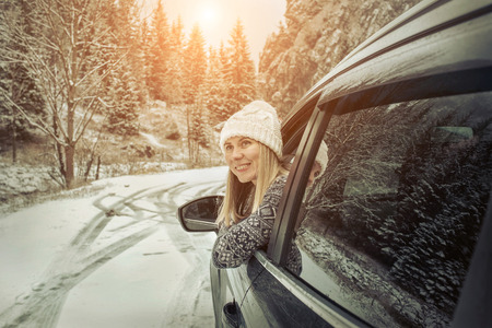 Photo for Woman at winter time. Yoyng female looking in window of her black car at snowly winter day. - Royalty Free Image