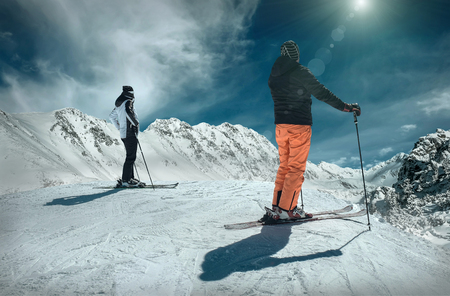 Men and Woman on the ski before sport action at sunny day around mountains under blue sky.