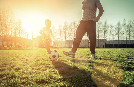 Photo pour Father and son playing together with ball in football under sun light. Green field in city park at sunny day. - image libre de droit