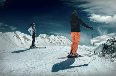 MAn and Woman on the ski before sport action at sunny day around mountains under blue sky.