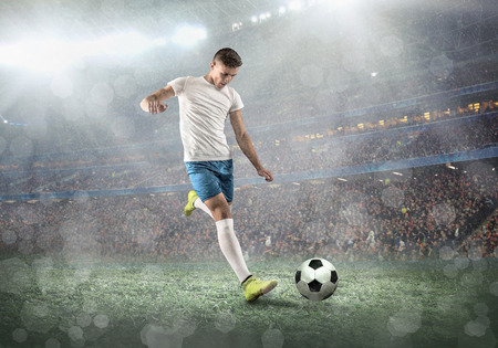 Photo pour Soccer player on a football field in dynamic action at summer day under sky with clouds. Sporty man is shooting the ball outdoor. - image libre de droit