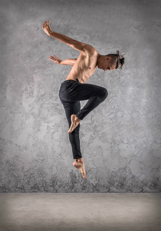 Photo for Man dancer, in beautiful dynamic jump action figure on the grunge background. - Royalty Free Image