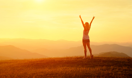 Foto de Happy woman with open arms stay on the peak of the mountain cliff edge under sunset light sky enjoying the success, freedom and bright future. - Imagen libre de derechos