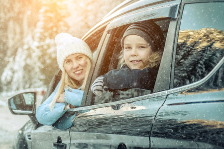 Foto de Happiness caucasian smilling boy with his mother looking out of black car window in sunny day at winter time near the forest. - Imagen libre de derechos