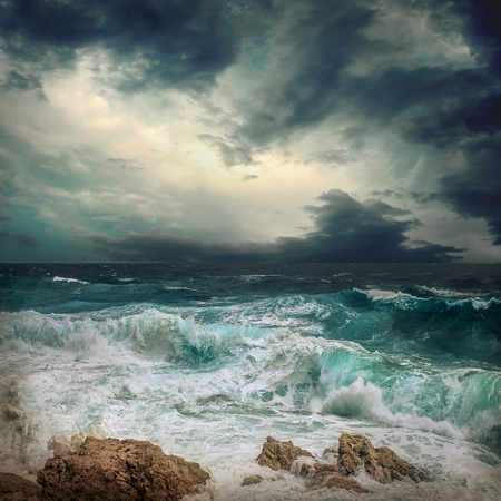 Foto de Stormy sea view  near coastline at evening time. Waves, splashed drops under dark dramatic sky. - Imagen libre de derechos
