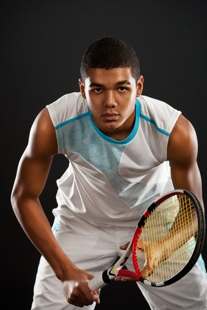 Young tennis player with racket ready to catch a tennis ball