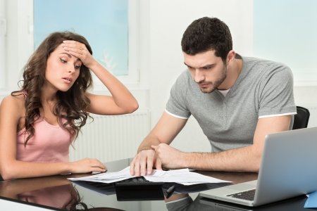 Couple, Man angry and upset after looking at credit card statement