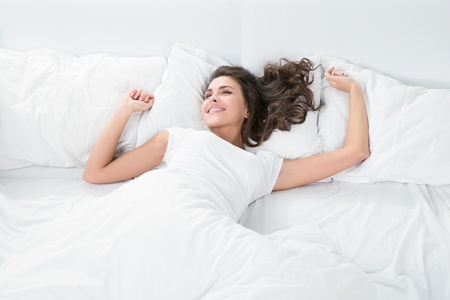 Photo pour young woman sleeping on the white linen in bed at home, top view - image libre de droit