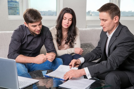 Photo for couple consults with agent, signing paperwork - Royalty Free Image