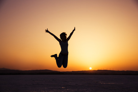 Photo pour silhouette of happy woman jumping in sunset - image libre de droit