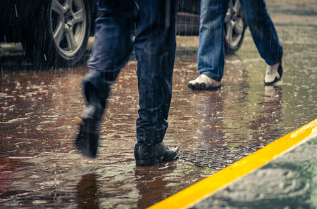 Photo for male feet stepping on wet from rain sidewalk in a city - Royalty Free Image