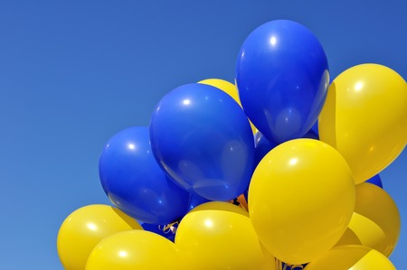 Foto de blue and yellow balloons in the city festival on blue sky background - Imagen libre de derechos