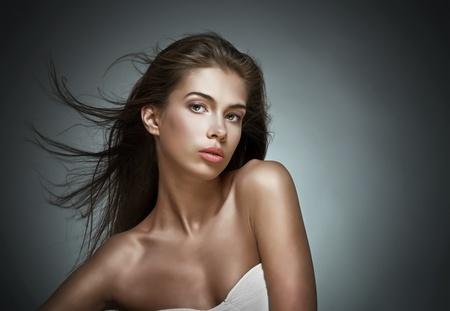 Beautiful woman with fluttering hair. On dark background.