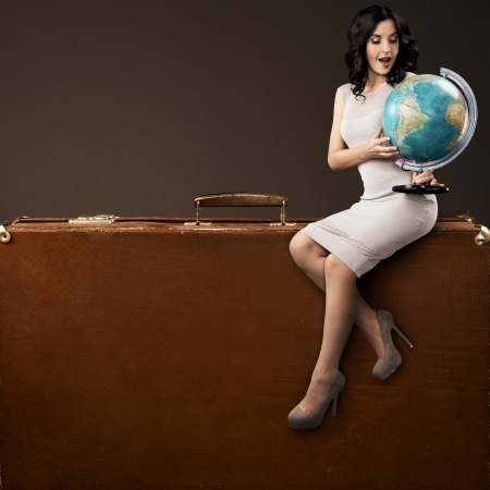 Foto de Lovely Woman With Globe In Hands Sitting On Huge Retro Suitcase. Space For Text - Imagen libre de derechos