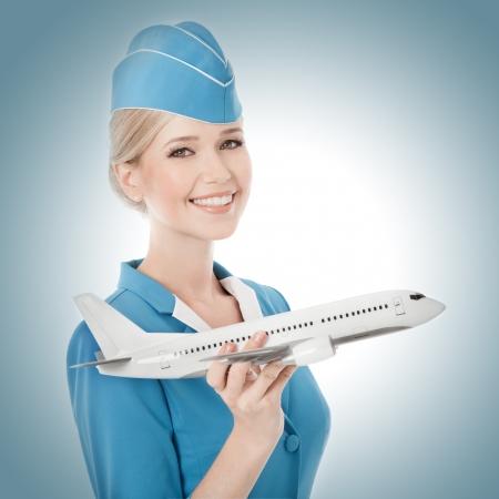 Photo pour Charming Stewardess Holding Airplane In Hand. - image libre de droit