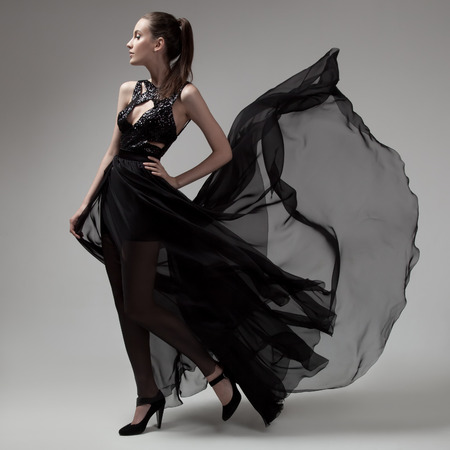 Photo pour Fashion woman in fluttering black dress. Gray background. - image libre de droit