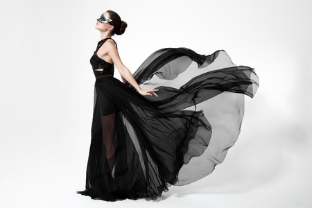 Photo pour Fashion woman in fluttering black dress. White background. - image libre de droit