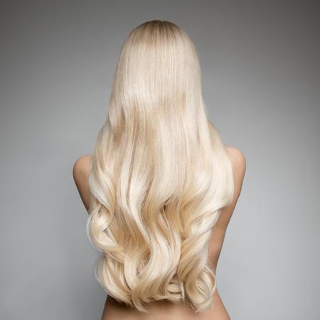 Photo pour Portrait Of Beautiful Young Blond Woman With Long Wavy Hair. Back view - image libre de droit