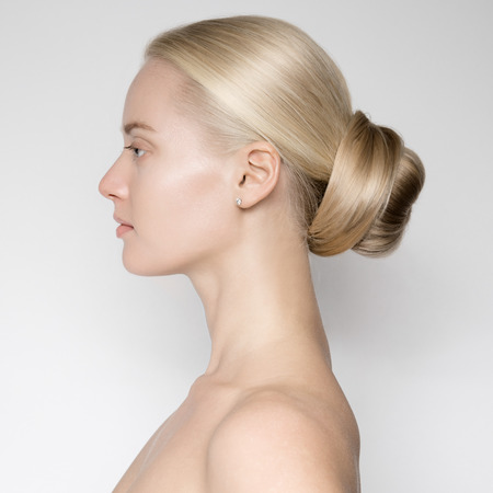 Photo for Portrait Of Beautiful Young Blond Woman With Bun Hairstуle. Side View - Royalty Free Image