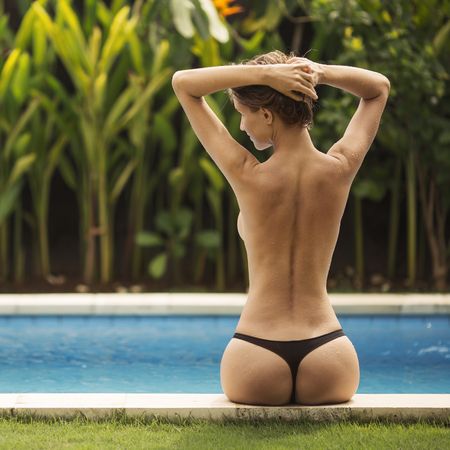 Photo for Young woman sunbathing near the pool. Back view. - Royalty Free Image
