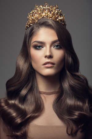 Photo pour Beautiful woman in gold crown on her head. Long wavy brown hair. - image libre de droit