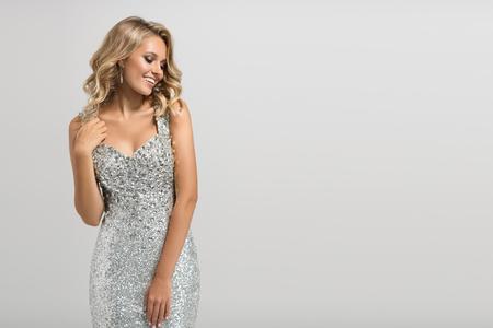 Photo pour Beautiful woman in shining silver dress on gray background. - image libre de droit