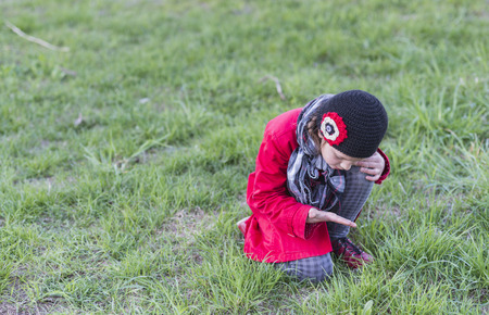 Photo for child girl seeking something on grass lawn by spring - Royalty Free Image