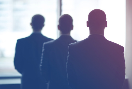 Foto de silhouette of three businessmen in the office - Imagen libre de derechos