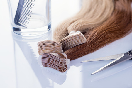 Photo pour Colored false hair with comb and scissors. Hair for hair extension on white background. - image libre de droit