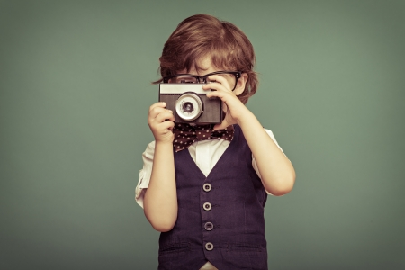 Photo pour Cheerful  smiling  child (boy) holding a instant camera  - image libre de droit