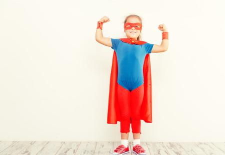 Photo pour Funny little power super hero child (girl) in a blue raincoat. Superhero concept - image libre de droit