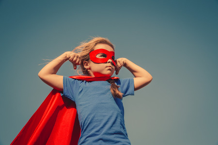 Foto de Funny little power super hero child (girl) in a red raincoat. Superhero concept. Instagram colors toning - Imagen libre de derechos