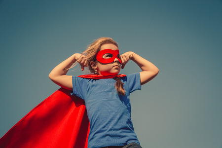 Photo pour Funny little power super hero child (girl) in a red raincoat. Superhero concept. Instagram colors toning - image libre de droit