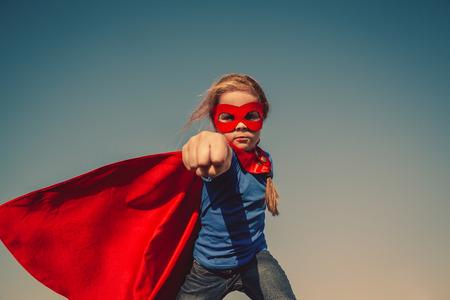 Foto de Funny little power super hero child (girl) in a red raincoat. Superhero concept. Instagram colors toning - Imagen libre de derechos