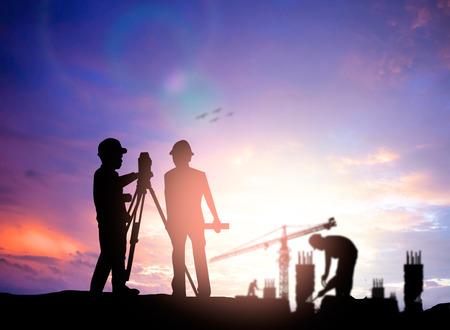 Photo pour silhouette survey engineer working  in a building site over Blurred construction worker on construction site - image libre de droit