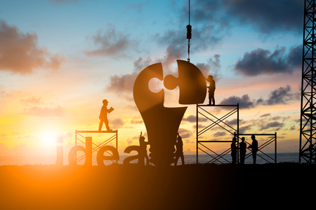 Photo pour Silhouette Team business engineer work connecting jigsaw puzzle piece together. team responsible for the idea of progress over blurred natural.Teamwork potential and motivate employee growth concept - image libre de droit