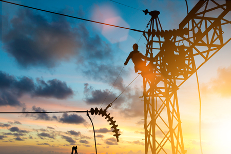 Foto de Silhouette electrician work installation of high voltage in high voltage stations safely and systematically over blurred natural background. - Imagen libre de derechos