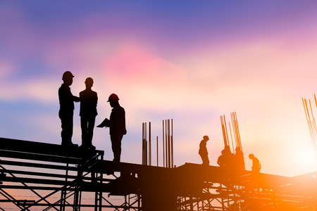 Photo for Silhouette engineer construction industry stands to talk about the work of the construction team that worked just as planned, construction or planned over blurred pastel background sunset industry. Heavy industry concept. - Royalty Free Image