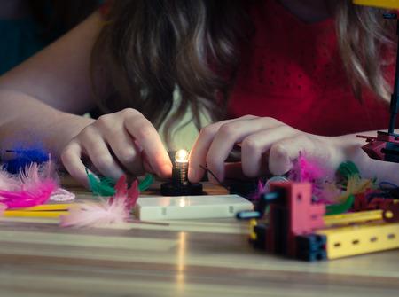 Foto de Female Child Wires a LIghtbulb Playing With Electronics Kit - Imagen libre de derechos