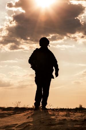 Foto de Silhouette of young soldier in military helmet against the sun - Imagen libre de derechos