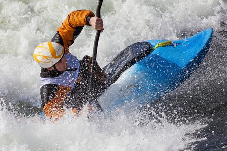 Foto de an active male kayaker rolling and surfing in rough water - Imagen libre de derechos