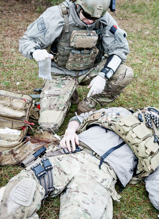 Foto de United States Army ranger treating the wounds of his injured fellow in arms - Imagen libre de derechos
