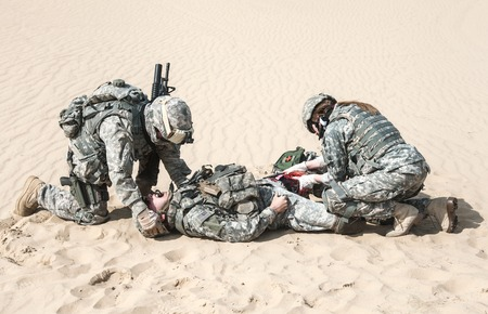Foto de United States paratroopers airborne infantrymen in the desert rescuing their brother - Imagen libre de derechos