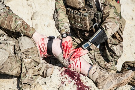 Foto de United States Army ranger medic treating the wounds of his injured fellow in arms in the mountains - Imagen libre de derechos